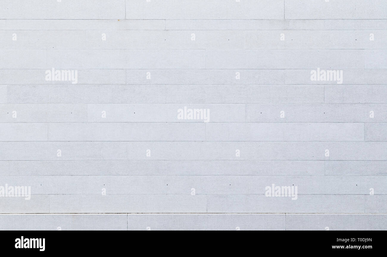 Full frame background of a new, modern and clean white or light gray stone wall or building exterior. Stock Photo