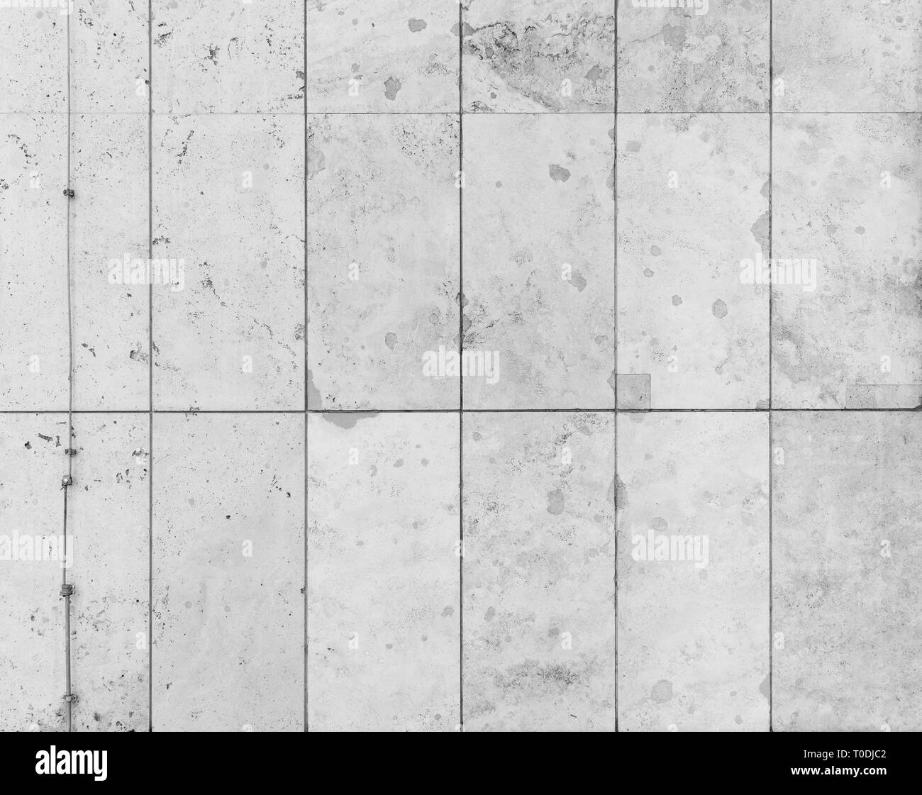 Full frame background of a modern and a bit broken wall or building exterior made of abstract stone slabs in black and white. Stock Photo