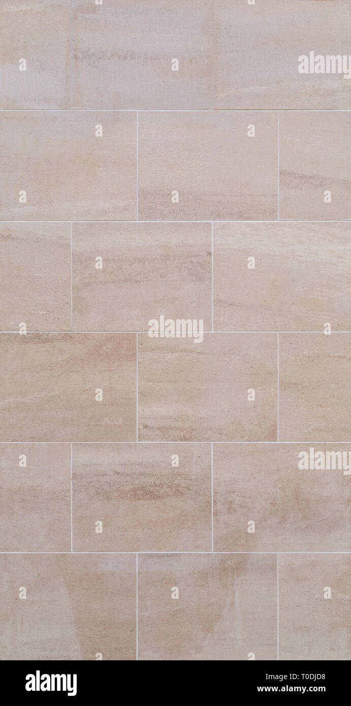 Full frame background of a new, modern and clean wall or building exterior made of light brown slabs. Stock Photo