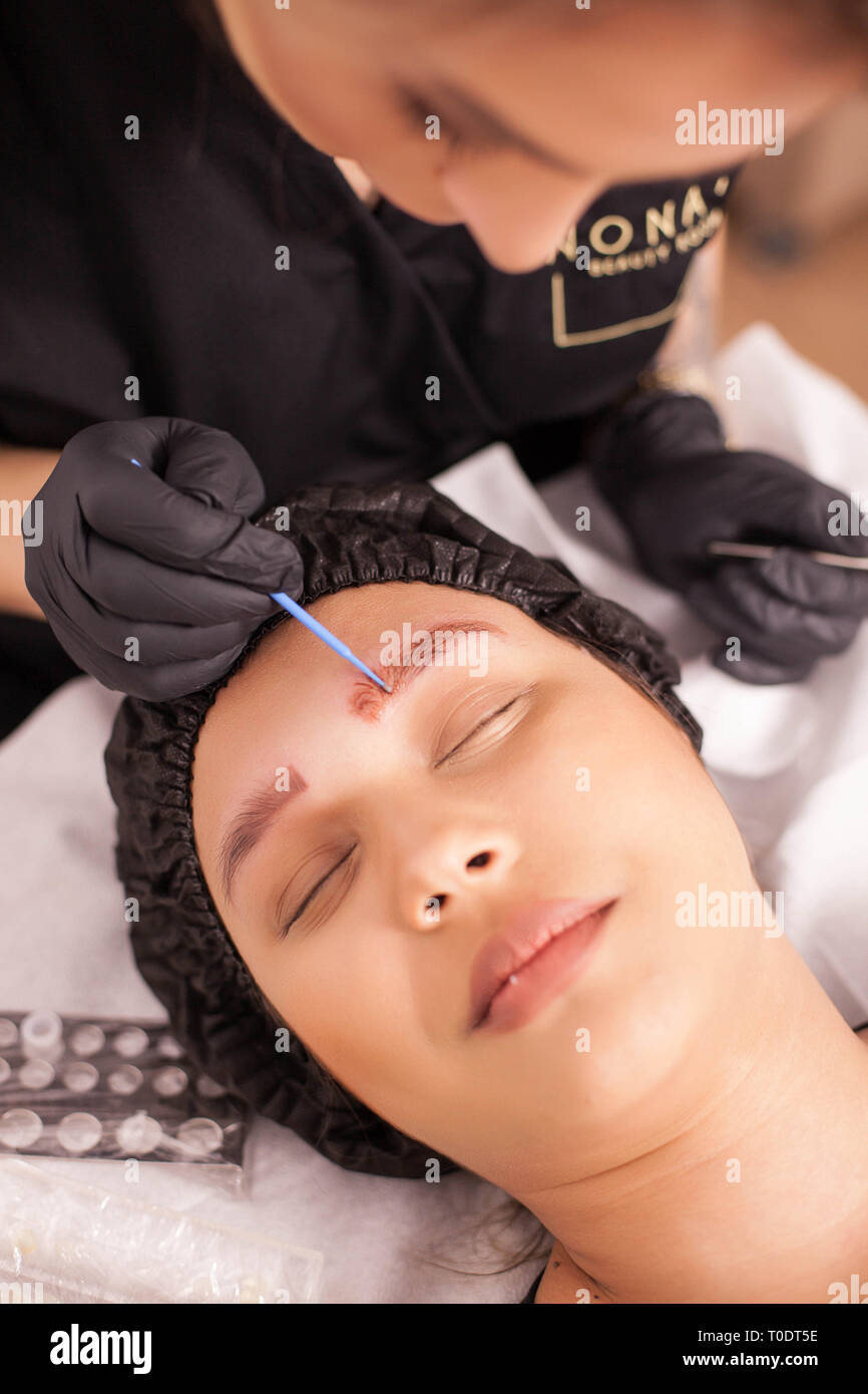Top view of beauty specialist applying treatment for tattoo