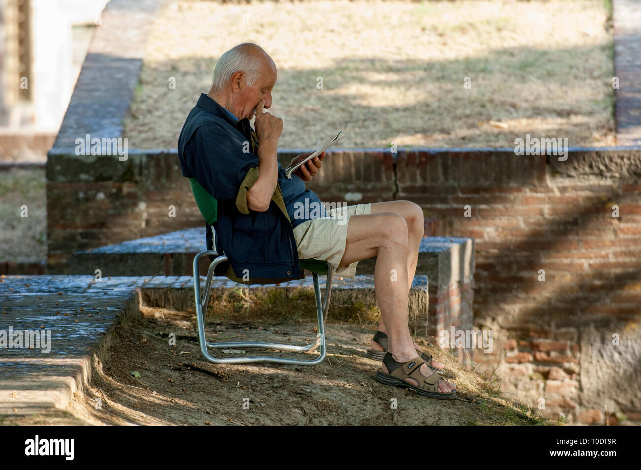 A man is sitting and reading in the park, Lucca, Italy. - Stock Image