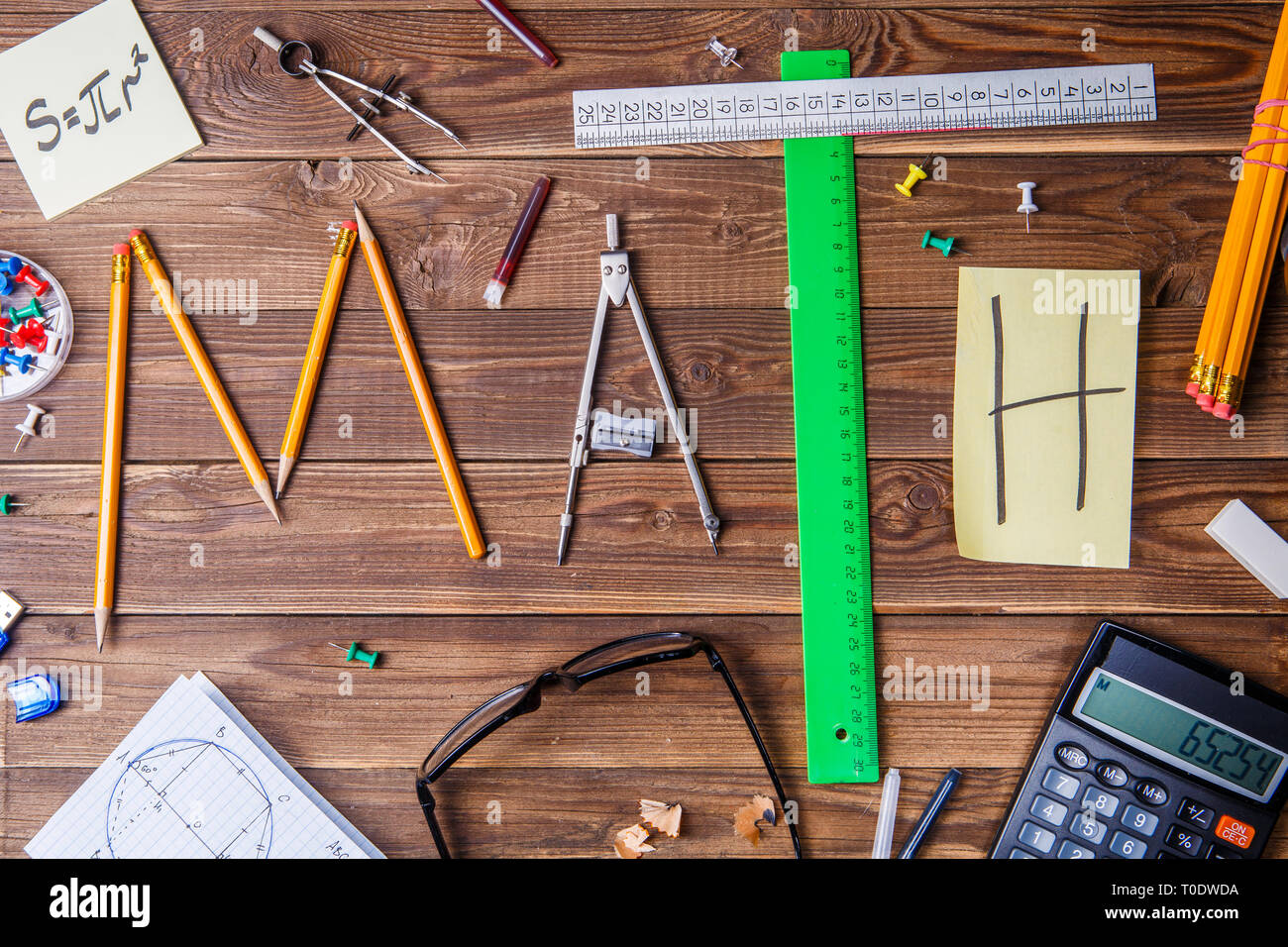 Text math composed of pencils, rulers, circular, sharpener and sticker with the letter - Stock Image