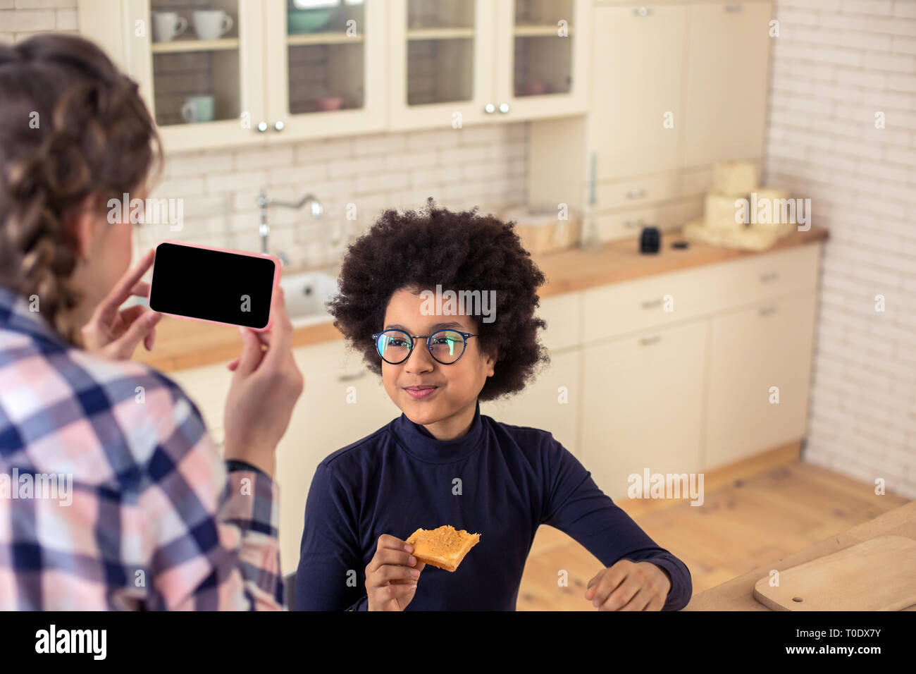 Pleased curly-haired kid keeping smile on his face - Stock Image