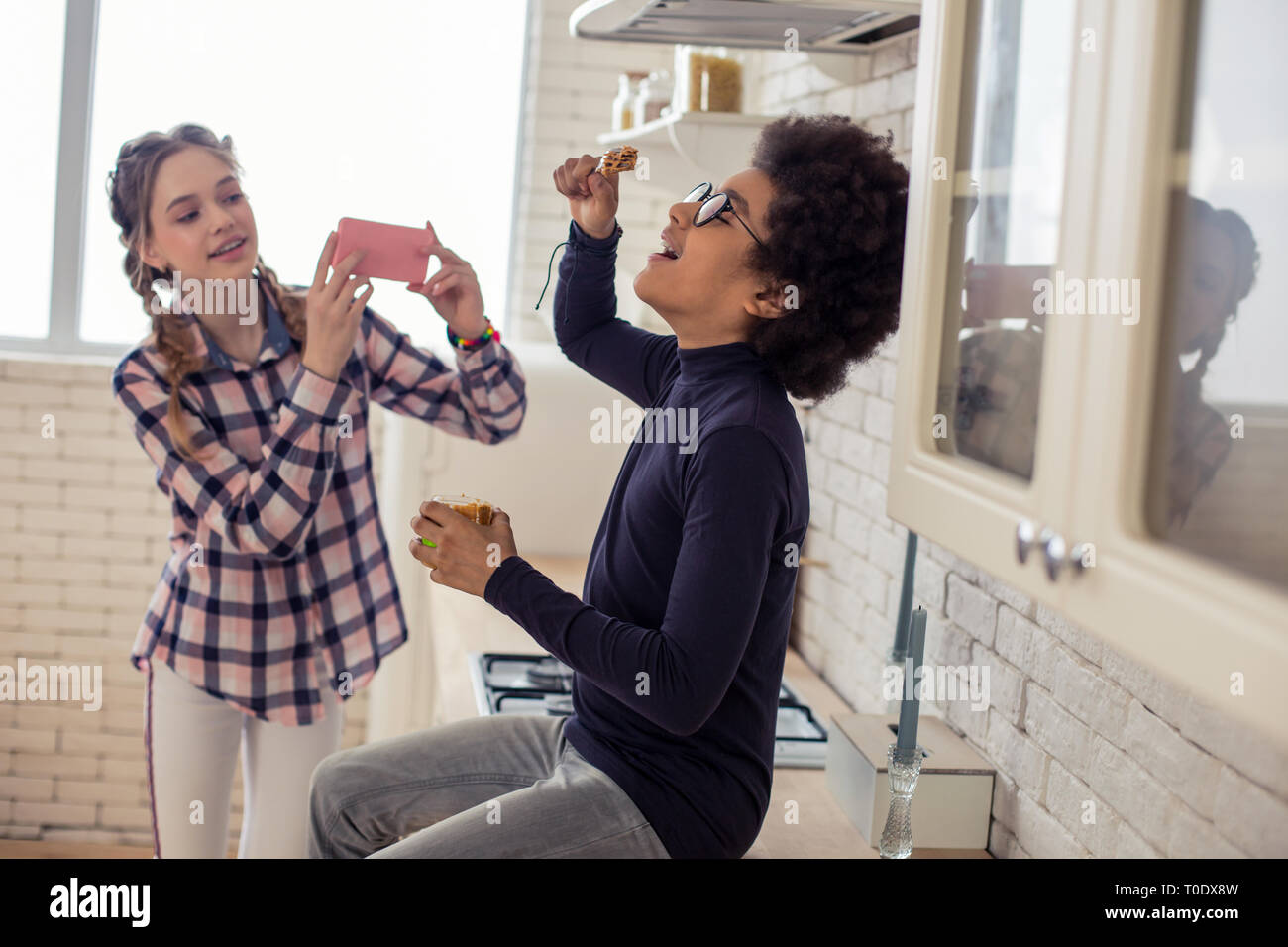 Joyful kids playing together with food in kitchen - Stock Image