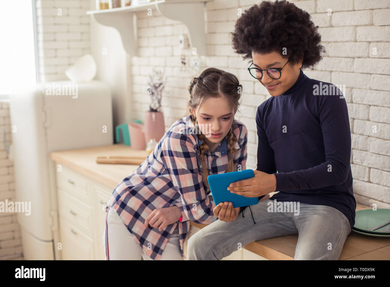 Attentive kids watching movie together on tablet - Stock Image