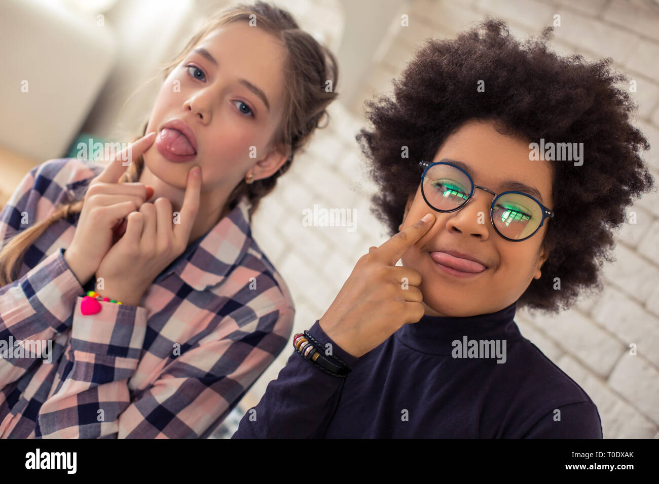 Playful teenagers making funny faces on camera - Stock Image