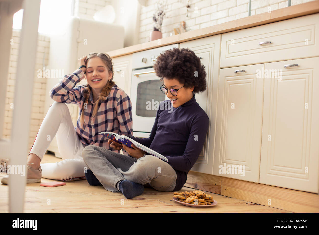 Positive delighted teenagers having rest after lessons - Stock Image