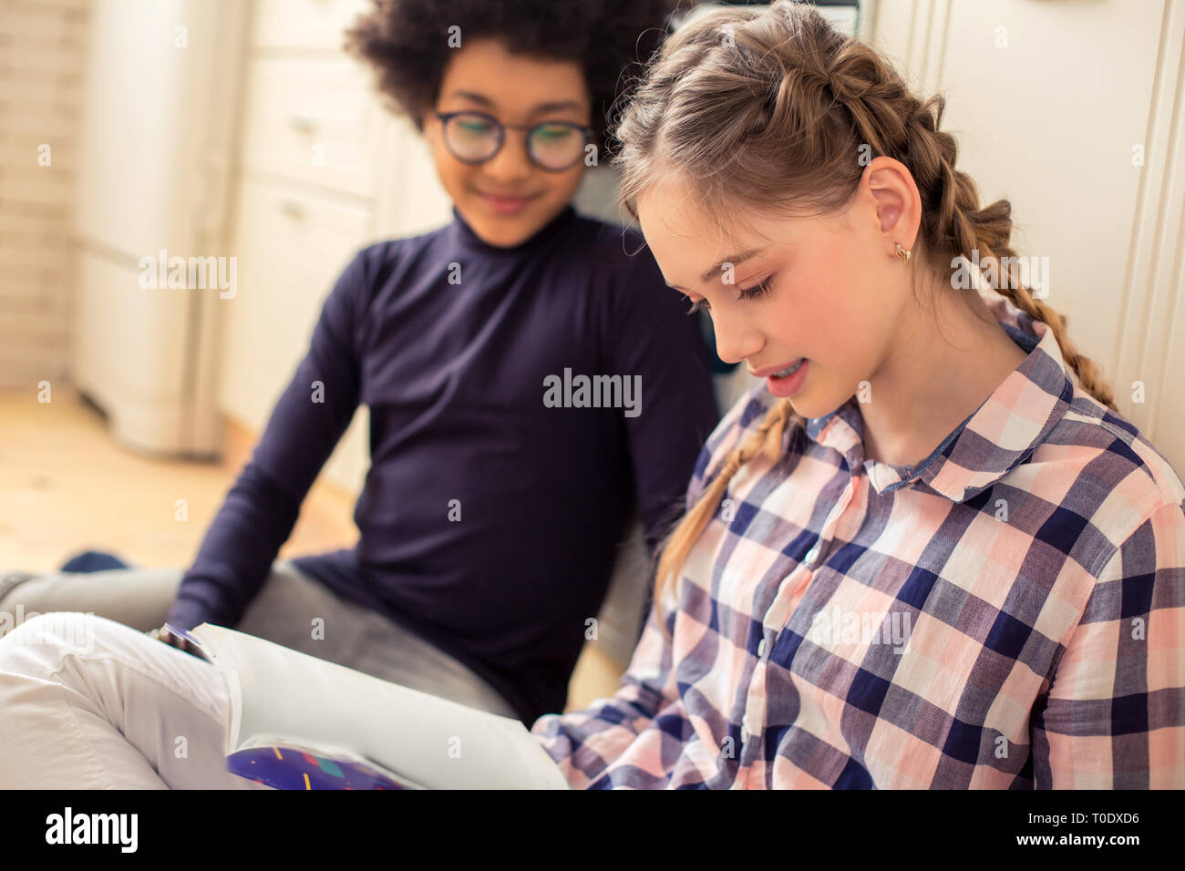 Close up of attentive girl that reading book - Stock Image