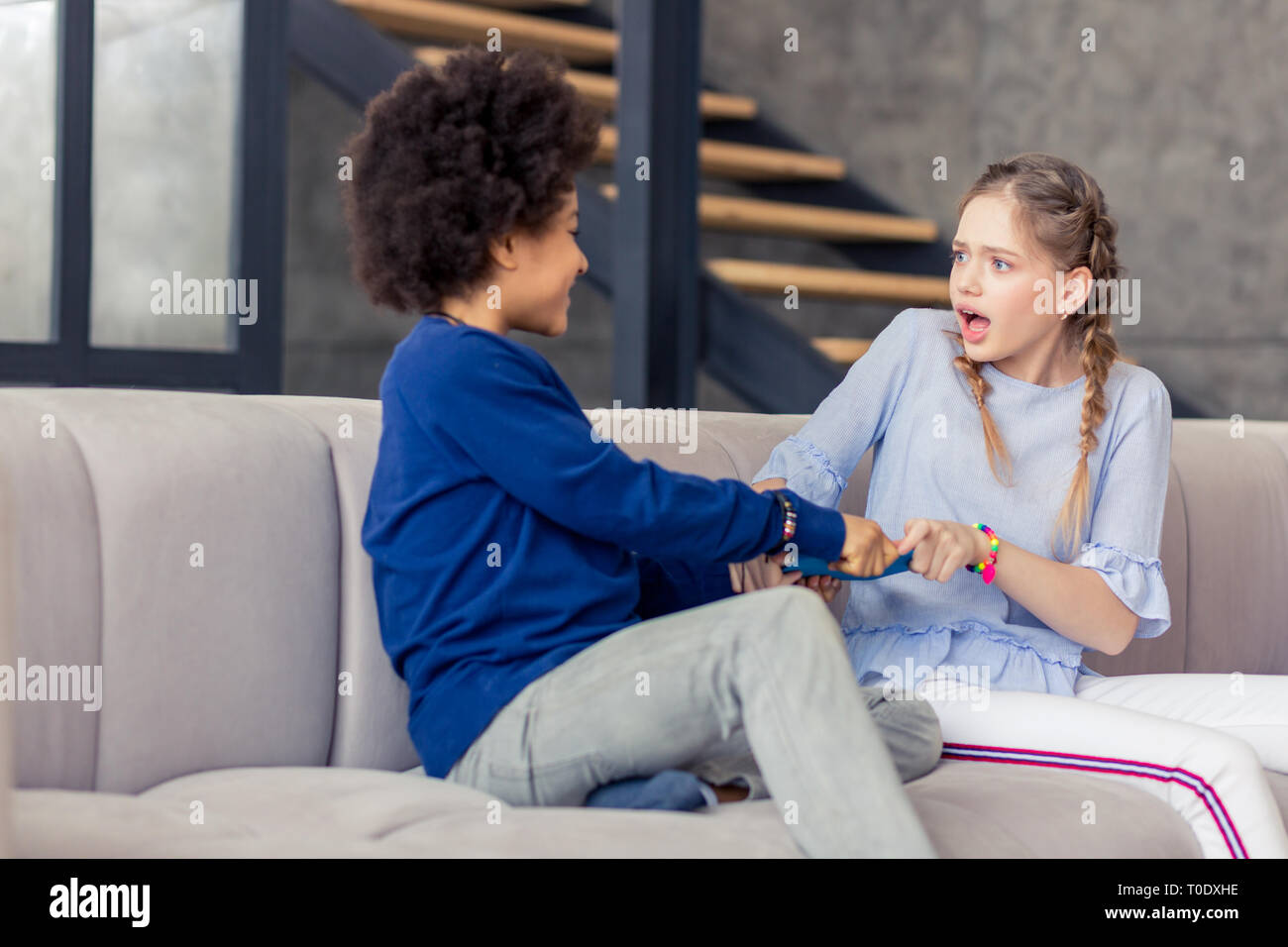 Shocked blonde teenager staring at her friend - Stock Image