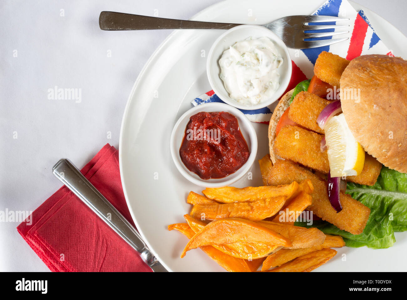 Typical English lunch snack of Fish fingers in a bun, Sweet potato fries, served with ketchup and Tartar. - Stock Image