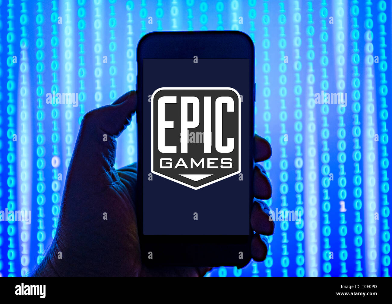 Person holding smart phone with Epic Games logo displayed on the screen. - Stock Image