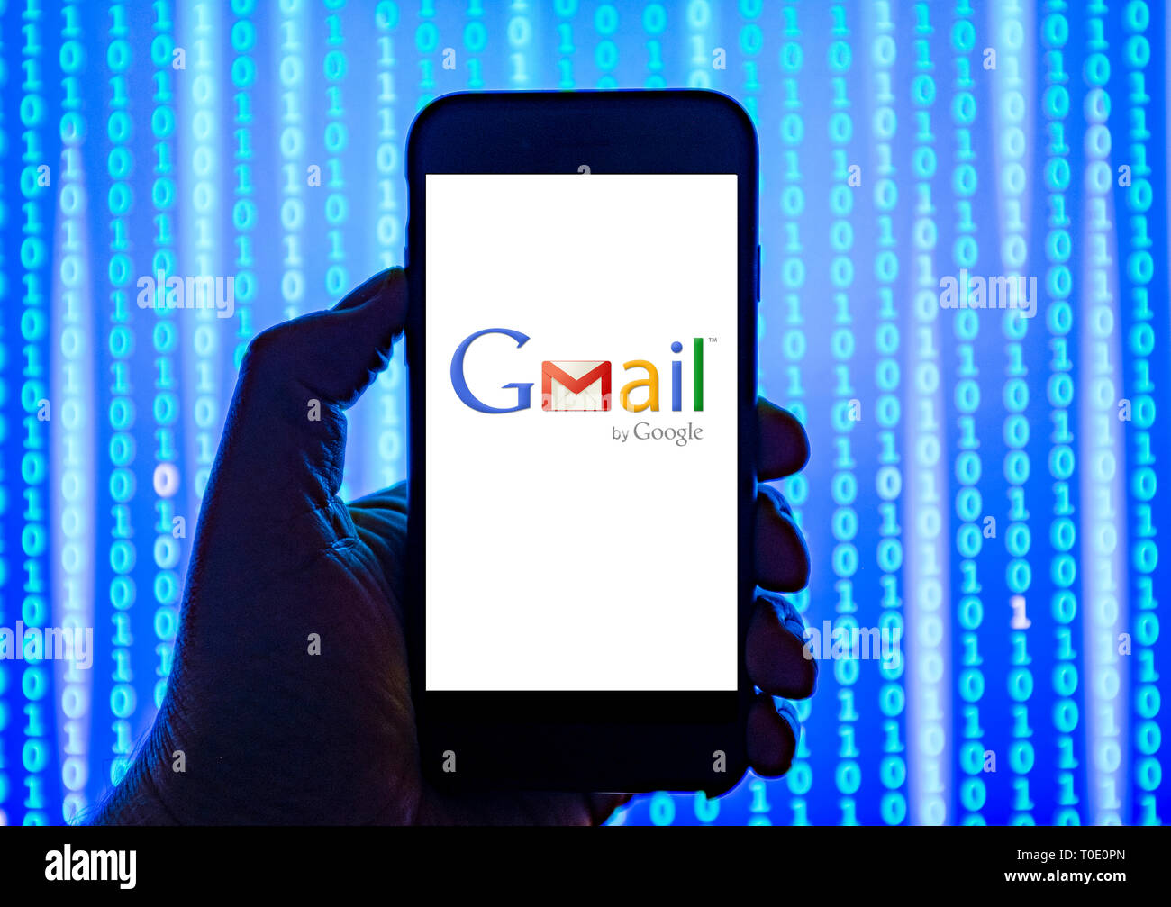 Person holding smart phone with Google Gmail email logo displayed on the screen. - Stock Image
