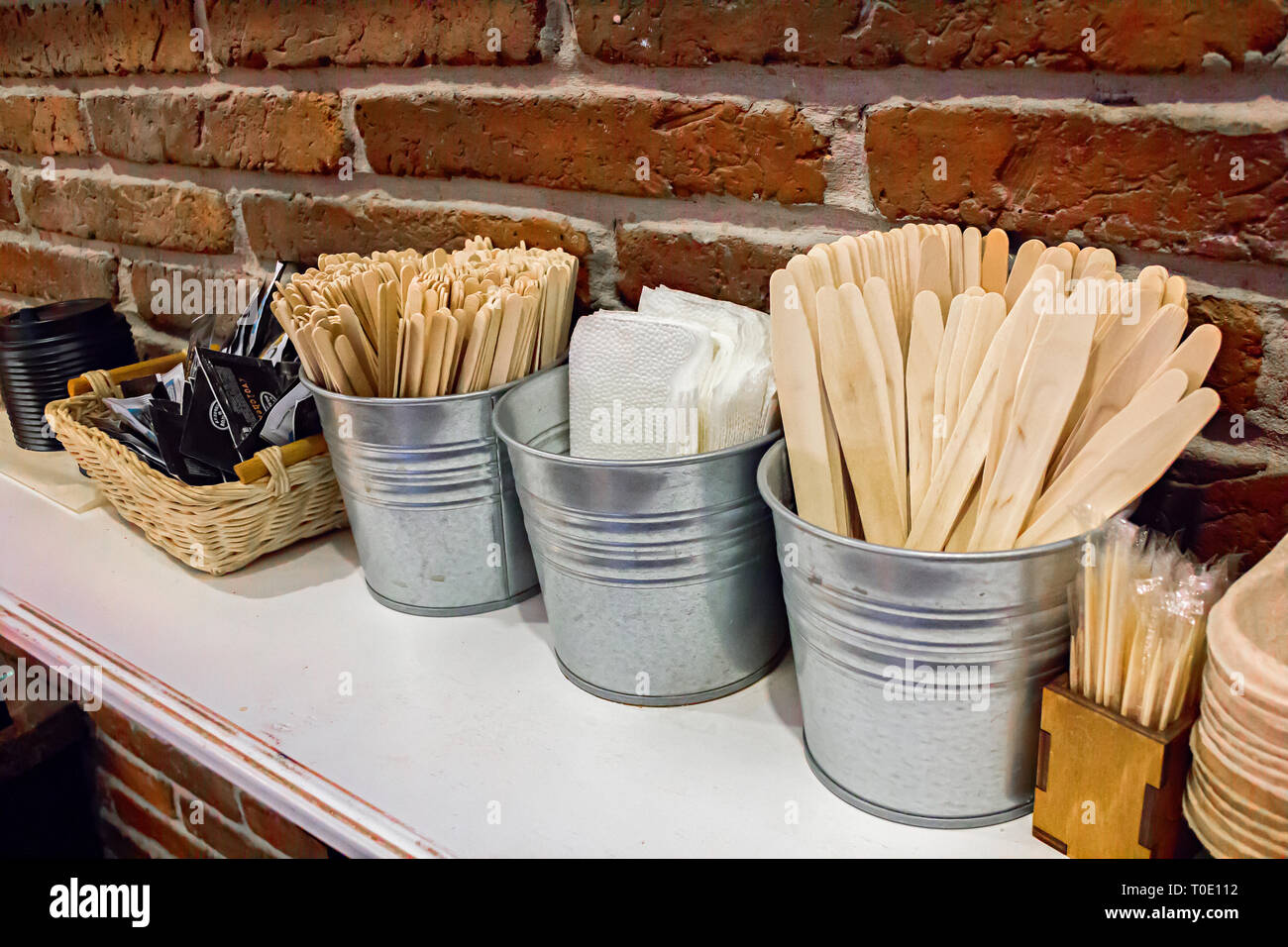 Close-up view of various disposable wooden sticks, wooden spoon, tooth sticks, cup covers, Take away boxes, napkins and sugar bags on wooden counter - Stock Image