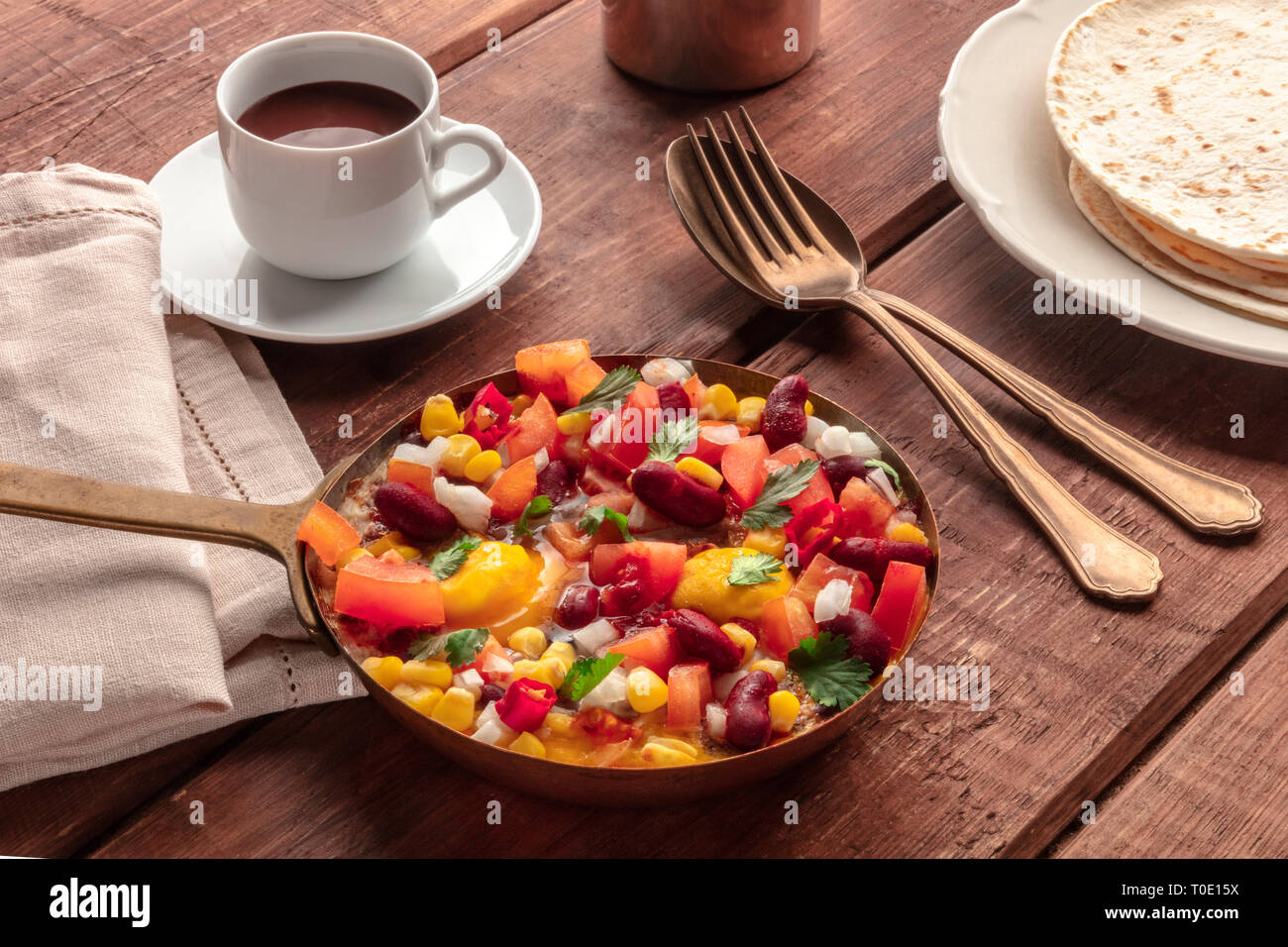 Mexican breakfast food. Huevos rancheros, the fried eggs, with the pico de gallo salad, hot chocolate, and tortillas - Stock Image