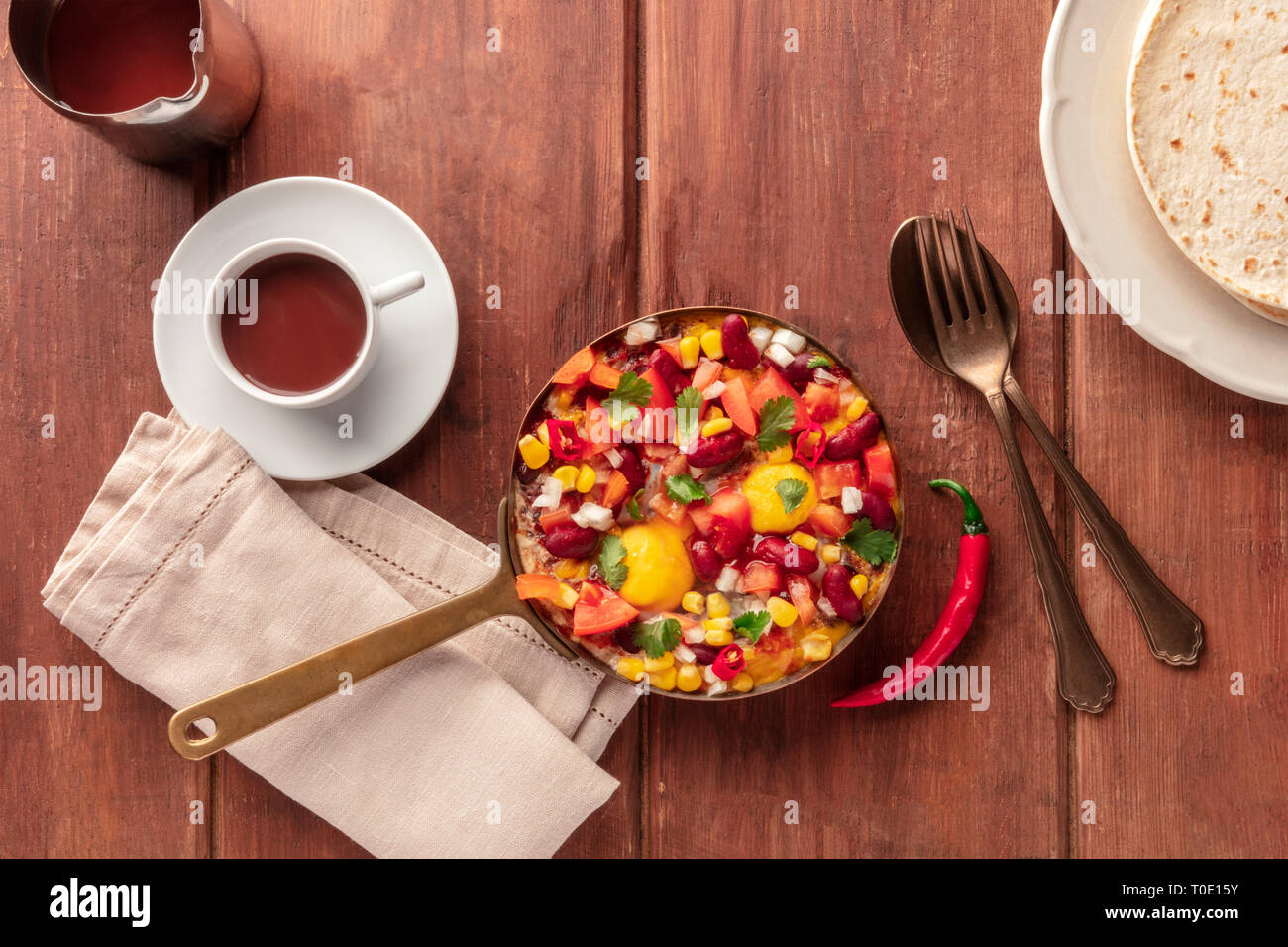 Mexican breakfast food. Huevos rancheros, the fried eggs, shot from the top with the pico de gallo salad, hot chocolate, and tortillas - Stock Image
