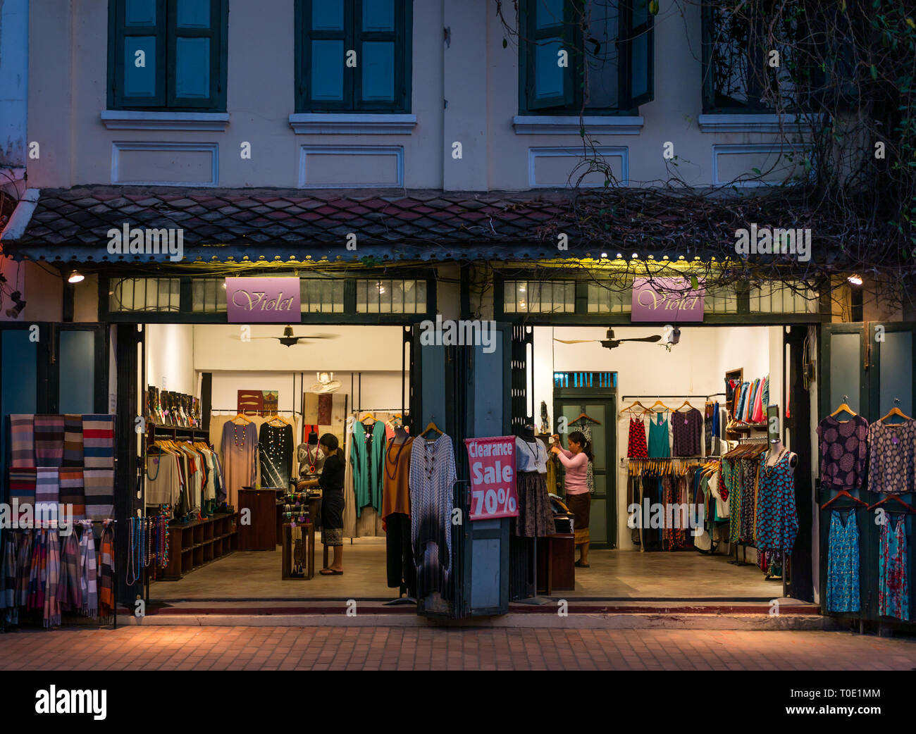 Woman's clothing shop called Violet selling dresses, shawls, and jewellry open at night, Luang Prabang, Laos, SE Asia - Stock Image