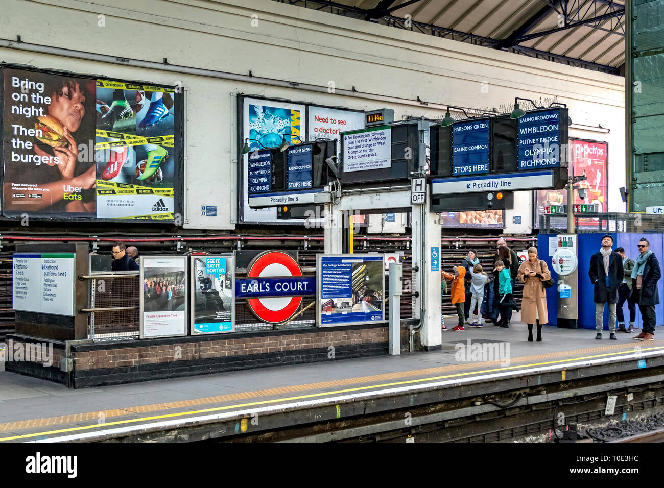 People waiting on the platform  for a District Line train at  Earls Court Underground Station , London SW5 - Stock Image