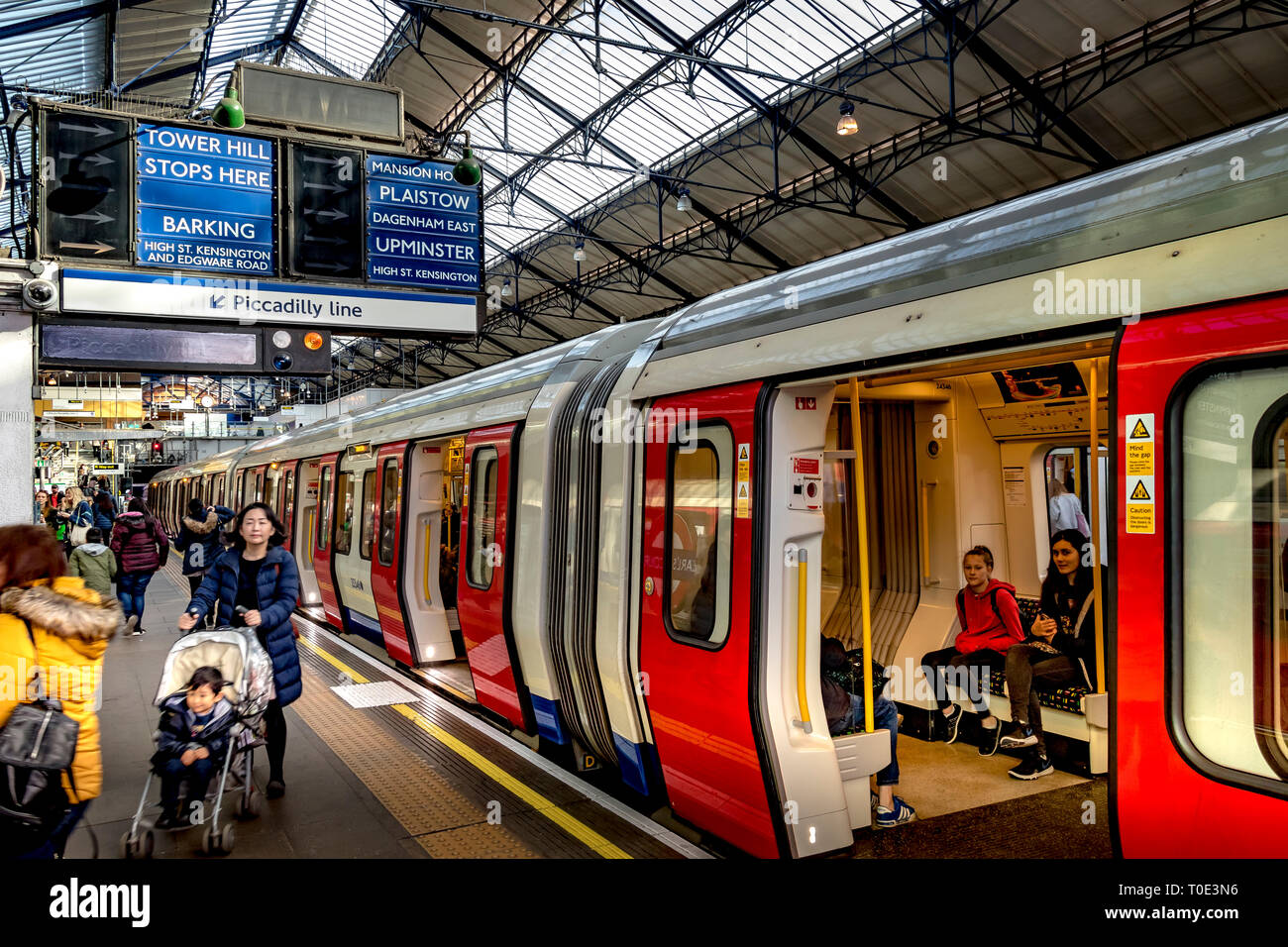 Two girls sitting on an S7 stock District Line train as a woman pushes a buggy on the platform at Earls's Court  Underground Station, London SW5 - Stock Image