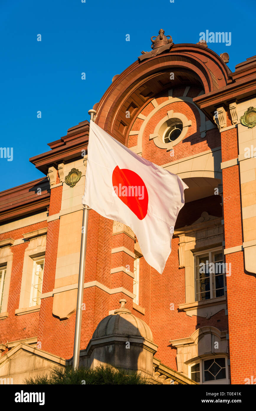 Tokyo Station old brick facade with Japan Nation Flag waving in front of it Stock Photo