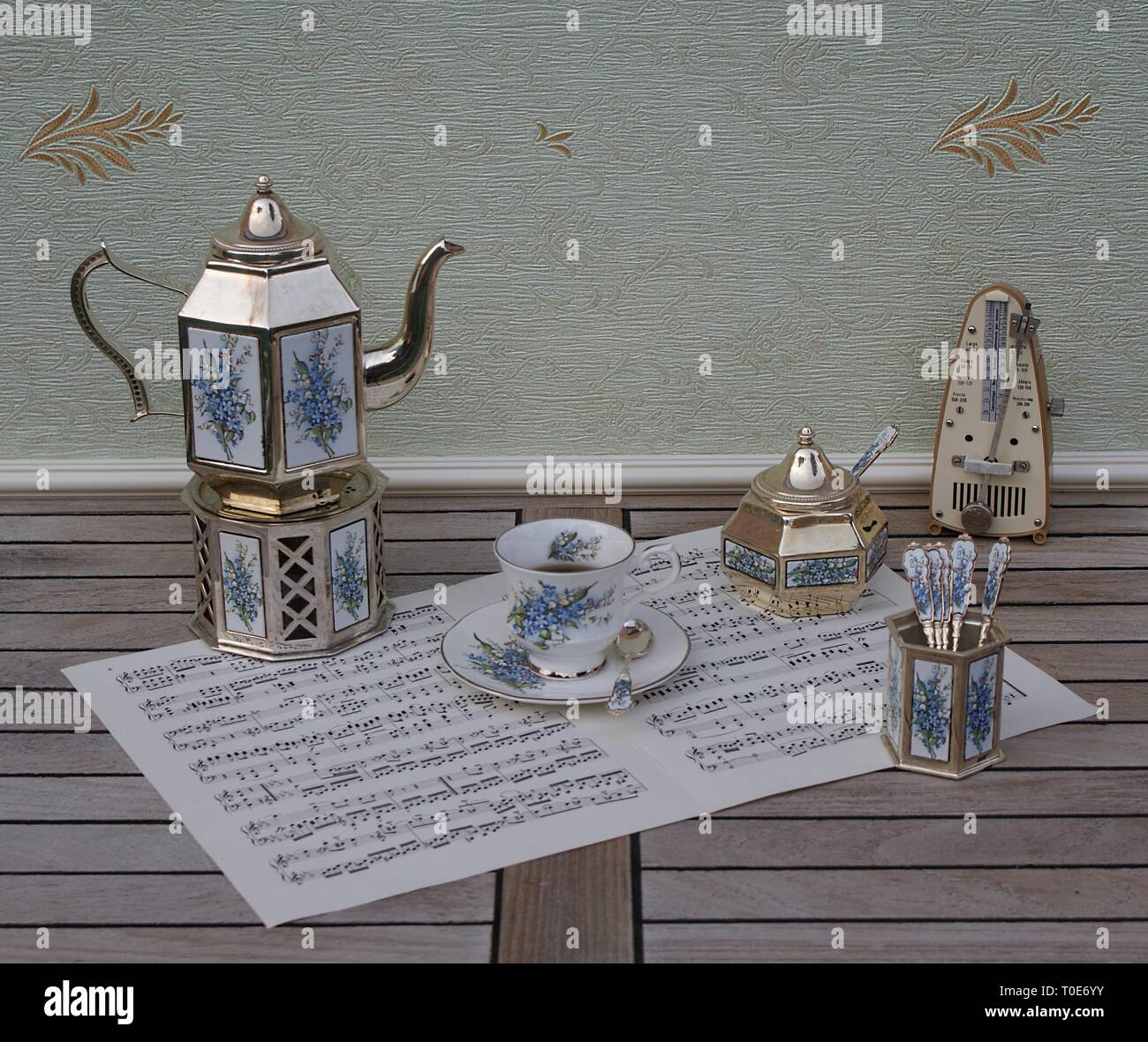 English tea set, silver-plated teapot on a silver stove, spoon vase, sugar bowl and sugar spoon and metronome for music on a sheet of music - Stock Image