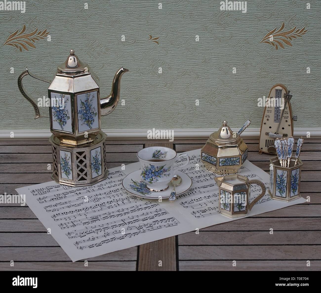 English tea set, silver-plated teapot on a silver stove, spoon vase and teaspoon, cream jug, sugar bowl and metronome for music on a sheet of music - Stock Image