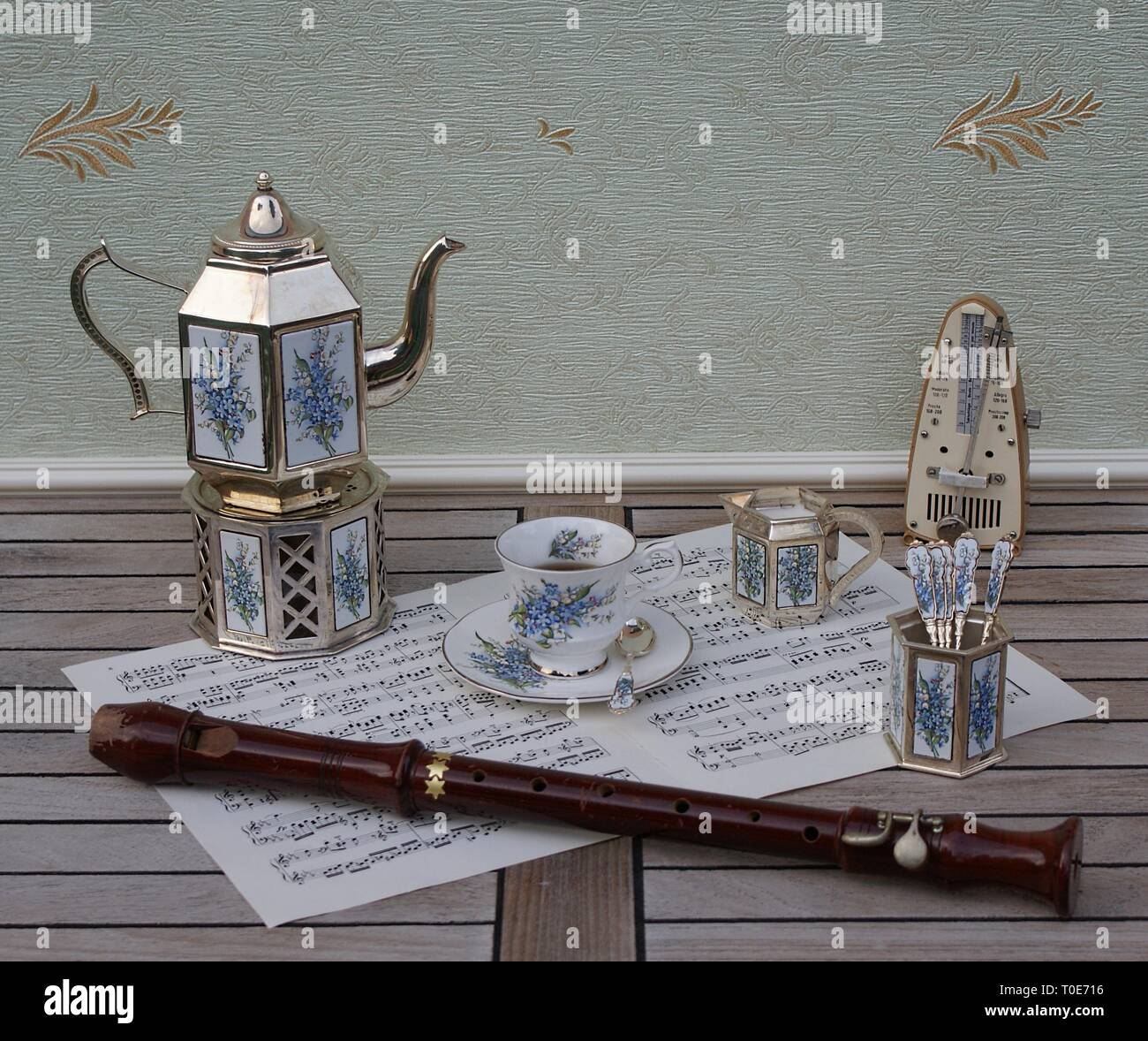 English teacup and saucer, silver-plated teapot, spoon vase, teaspoon, cream jug and metronome for music and a block flute on a sheet of music - Stock Image