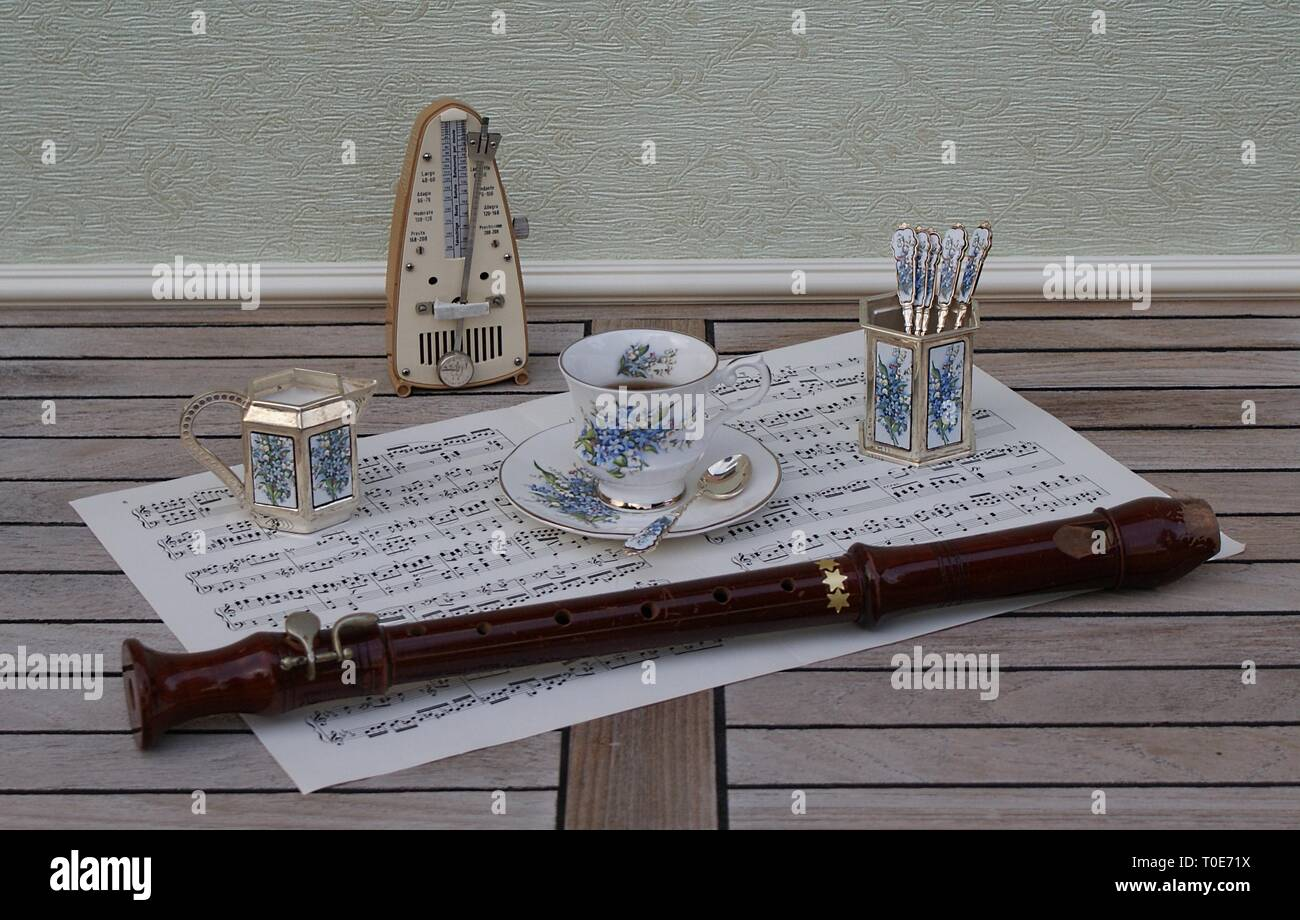 English teacup and saucer, spoon vase, teaspoon and cream jug, metronome for music and a block flute on a sheet of music - Stock Image