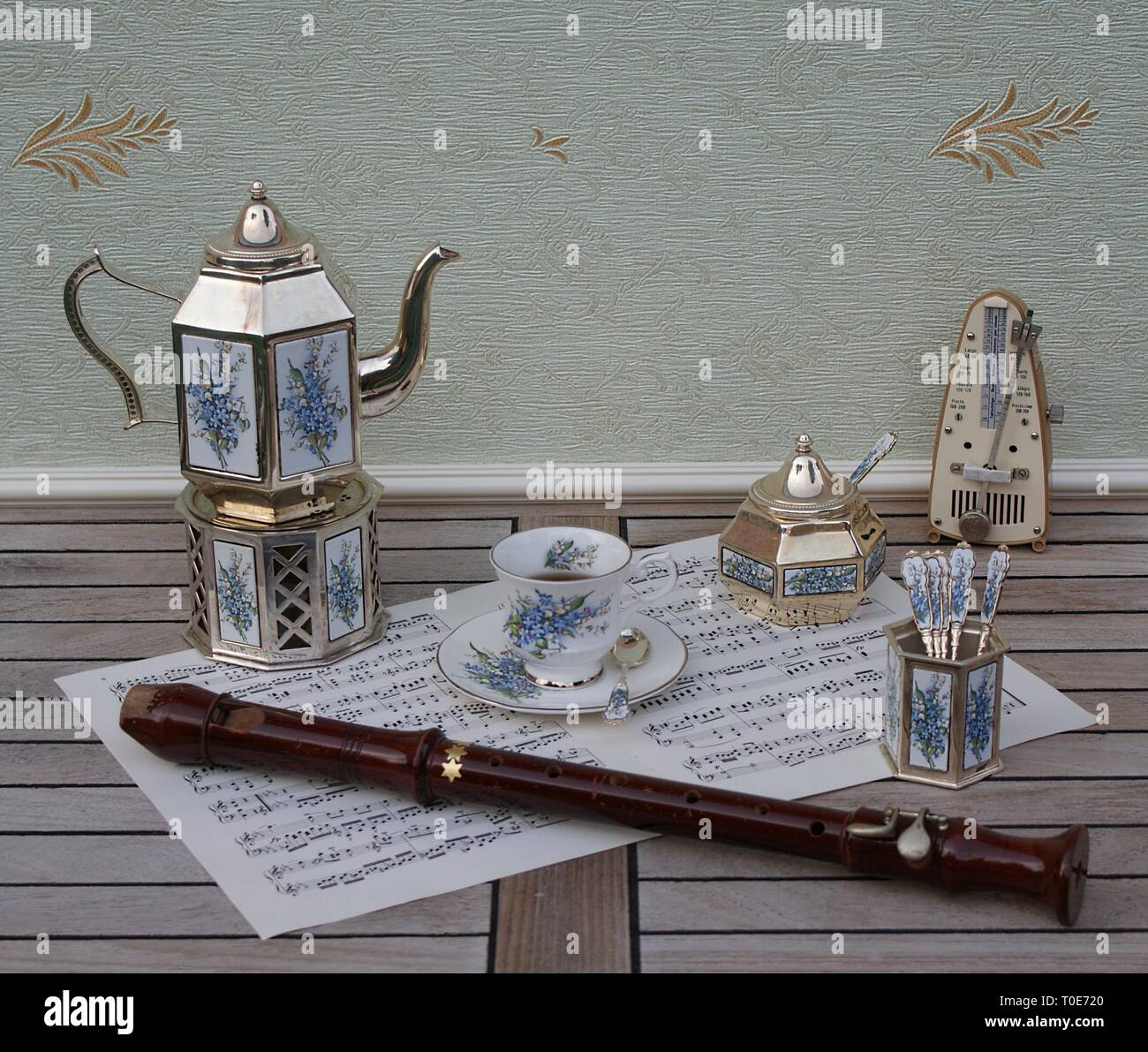 English tea set, silver-plated teapot on a silver stove, spoon vase and teaspoon, sugar bowl, metronome for music, a block flute on a sheet of music - Stock Image