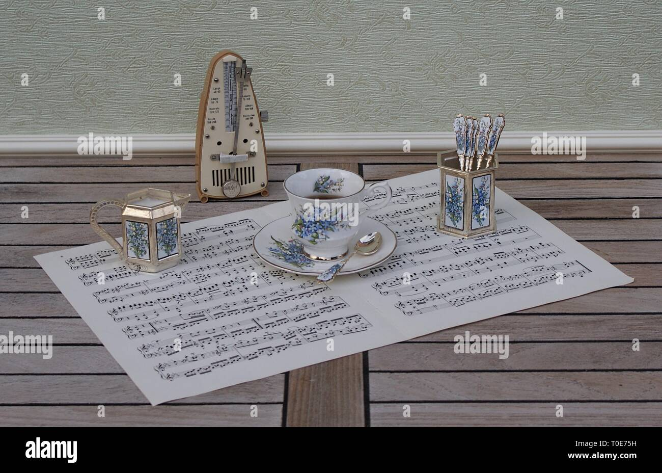 English teacup and saucer, spoon vase, teaspoon and cream jug and metronome for music on a sheet of music - Stock Image