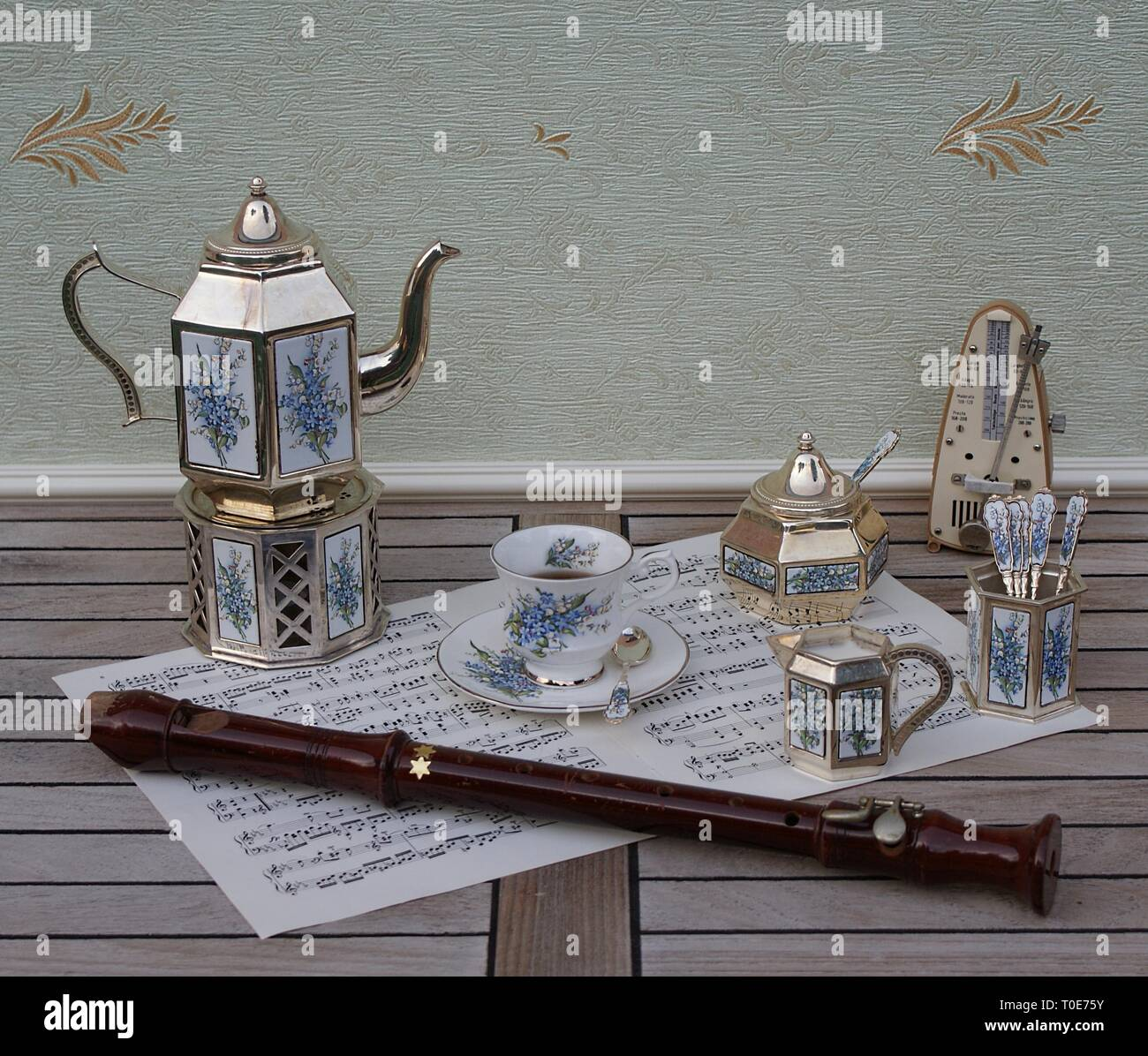 English tea set, silver-plated teapot, spoon vase, cream jug, sugar bowl and sugar spoon, metronome for music and a block flute on a sheet of music - Stock Image