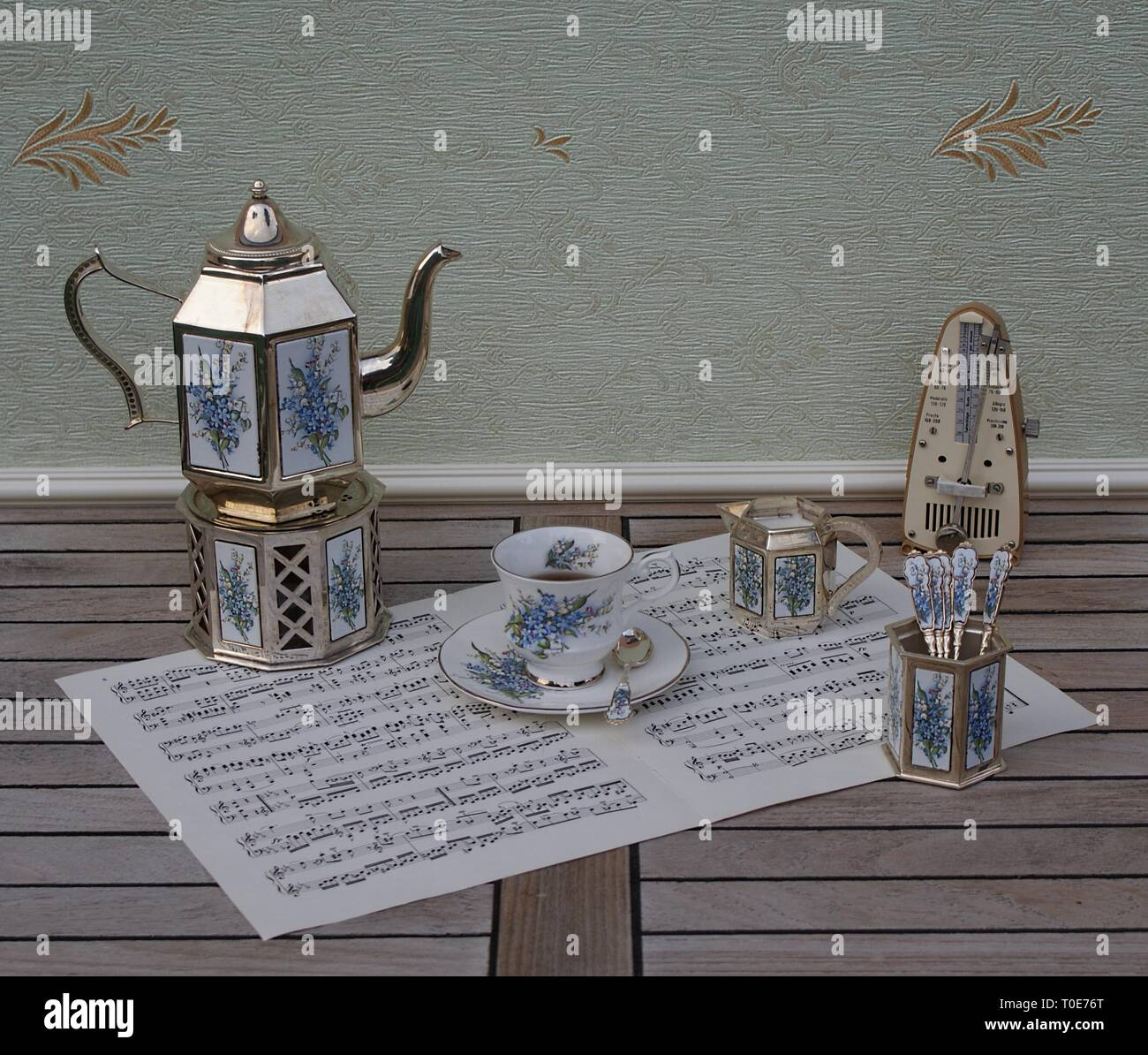 English teacup and saucer, silver-plated teapot on a silver stove, spoon vase, teaspoon and cream jug and metronome for music on a sheet of music - Stock Image