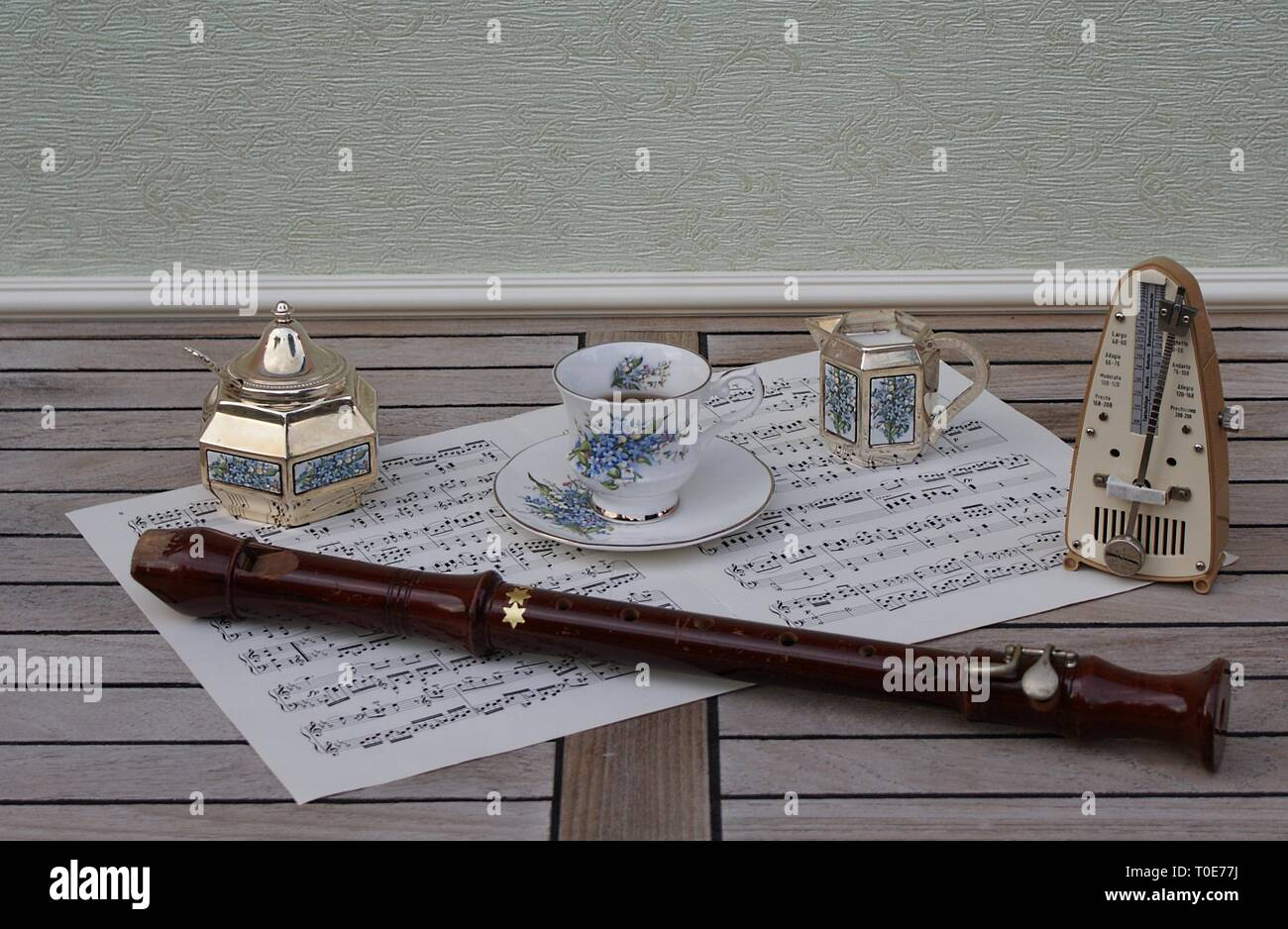 English teacup and saucer, cream jug, sugar bowl and sugar spoon, with floral decor, and metronome for music and a block flute on a sheet of music - Stock Image