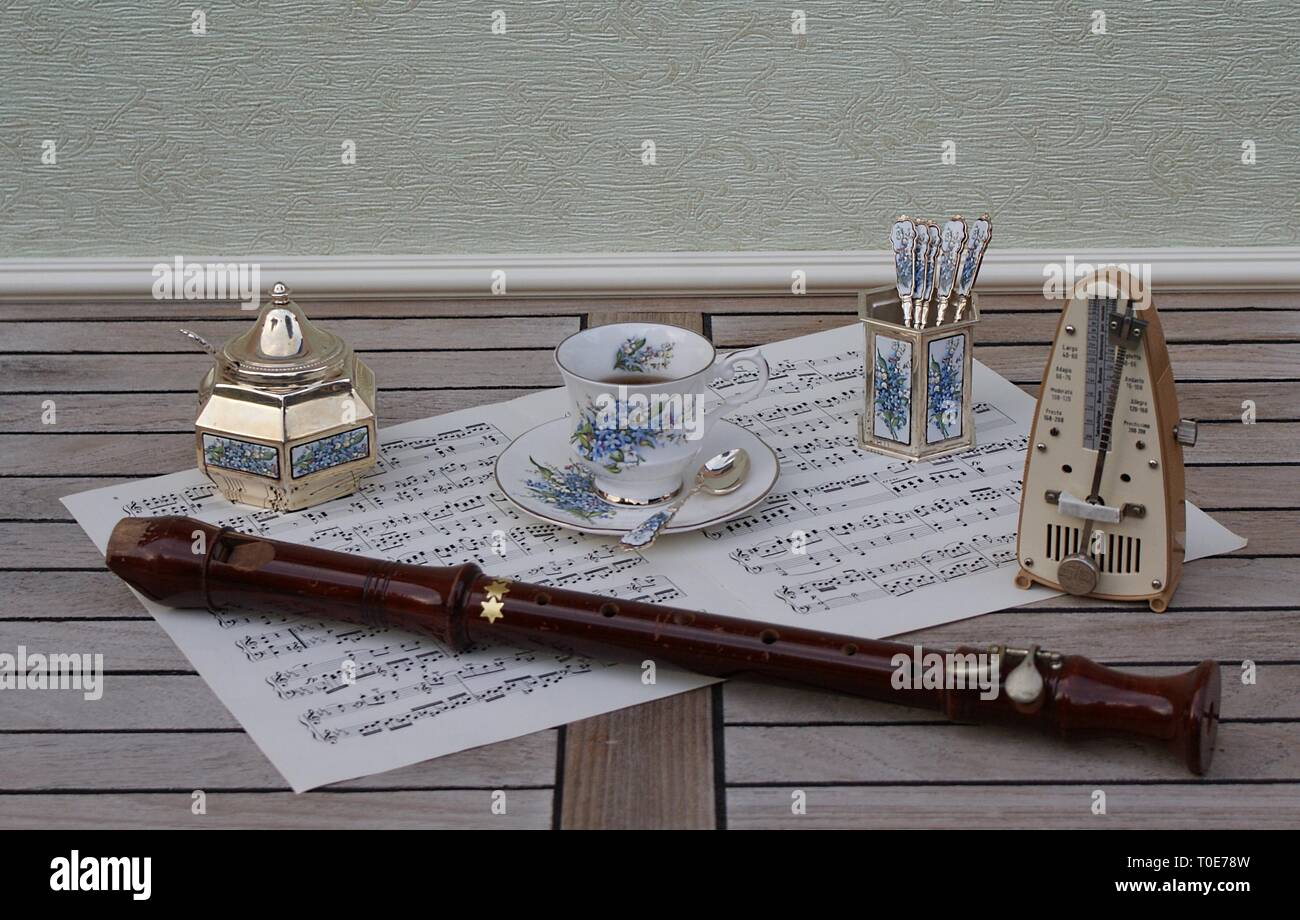 English teacup, spoon vase and teaspoon, sugar bowl and sugar spoon, with floral décor, metronome for music and a block flute on a sheet of music - Stock Image