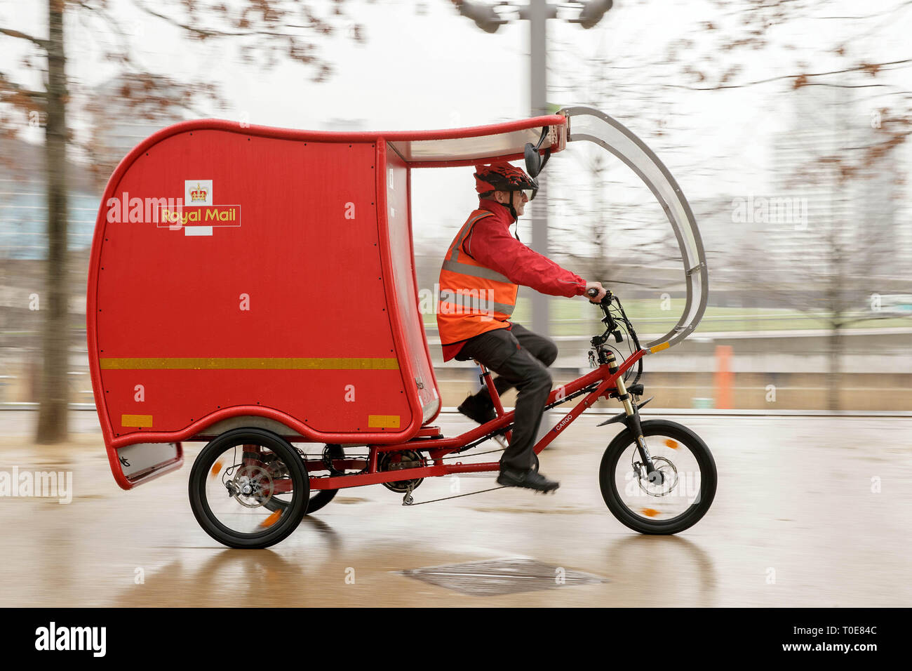 EDITORIAL USE ONLY Postman Nigel Roughty rides at the unveiling of the zero-carbon emission e-Trikes, which are predominantly powered by a combination of solar, battery and brake technology, and will be trialled by Royal Mail in Stratford in east London, Cambridge and Sutton Coldfield at the end of the month. - Stock Image