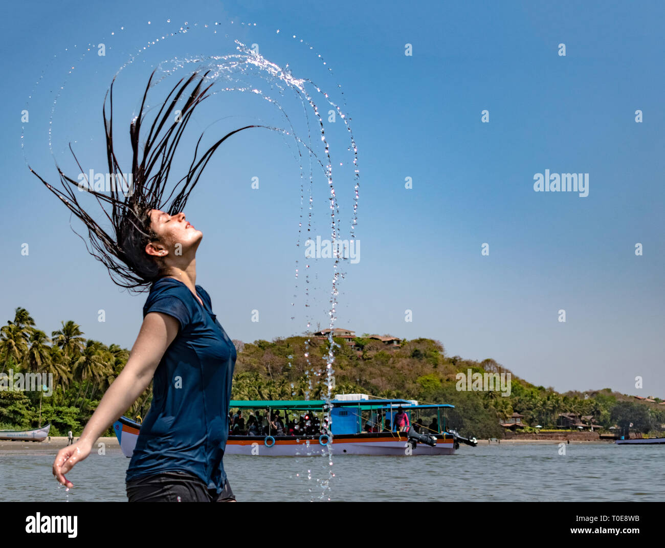 Beautiful Indian girl on solo travel is enjoying her vacations by having fun at beach by whipping her long black hairs off the water and whirling it. - Stock Image