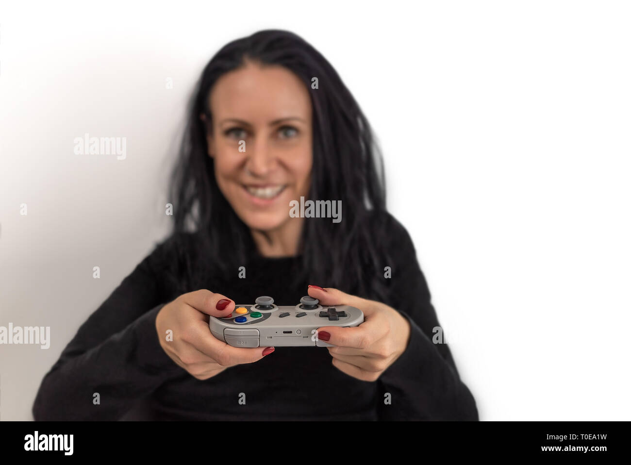 Young woman with red nail polish  playing video game on a retro wireless gaming controller with a happy and concentrated facial expressions Stock Photo