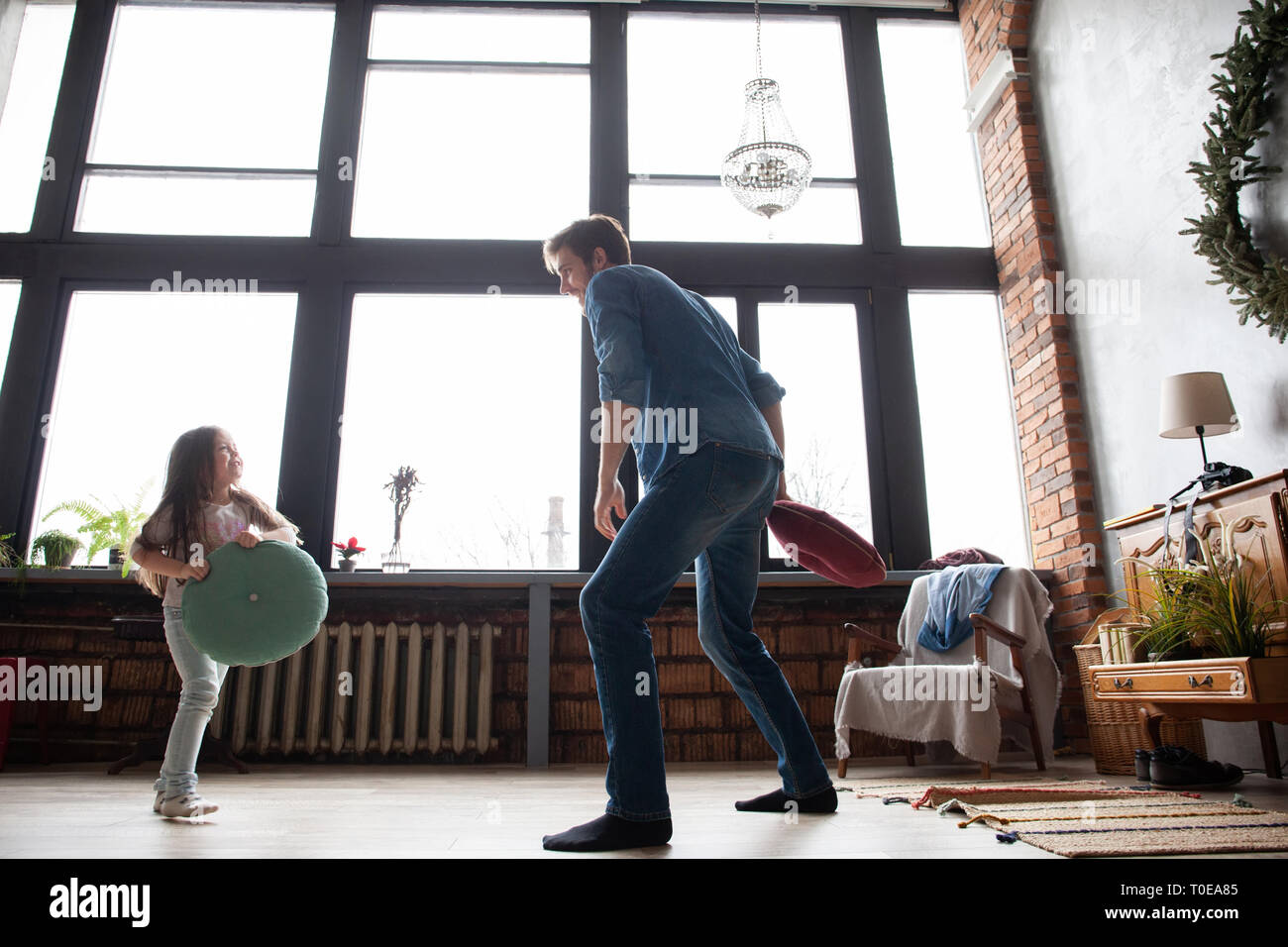 Father and his child playing together. Girl and dad having fun and fighting pillows. Family holiday and togetherness. Stock Photo