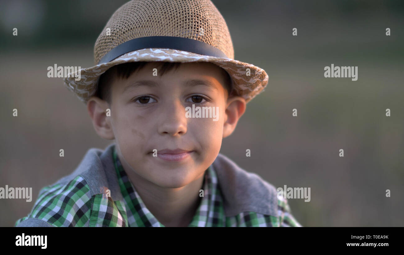 portrait of a village boy in a straw hat looking into the camera at sunset - Stock Image
