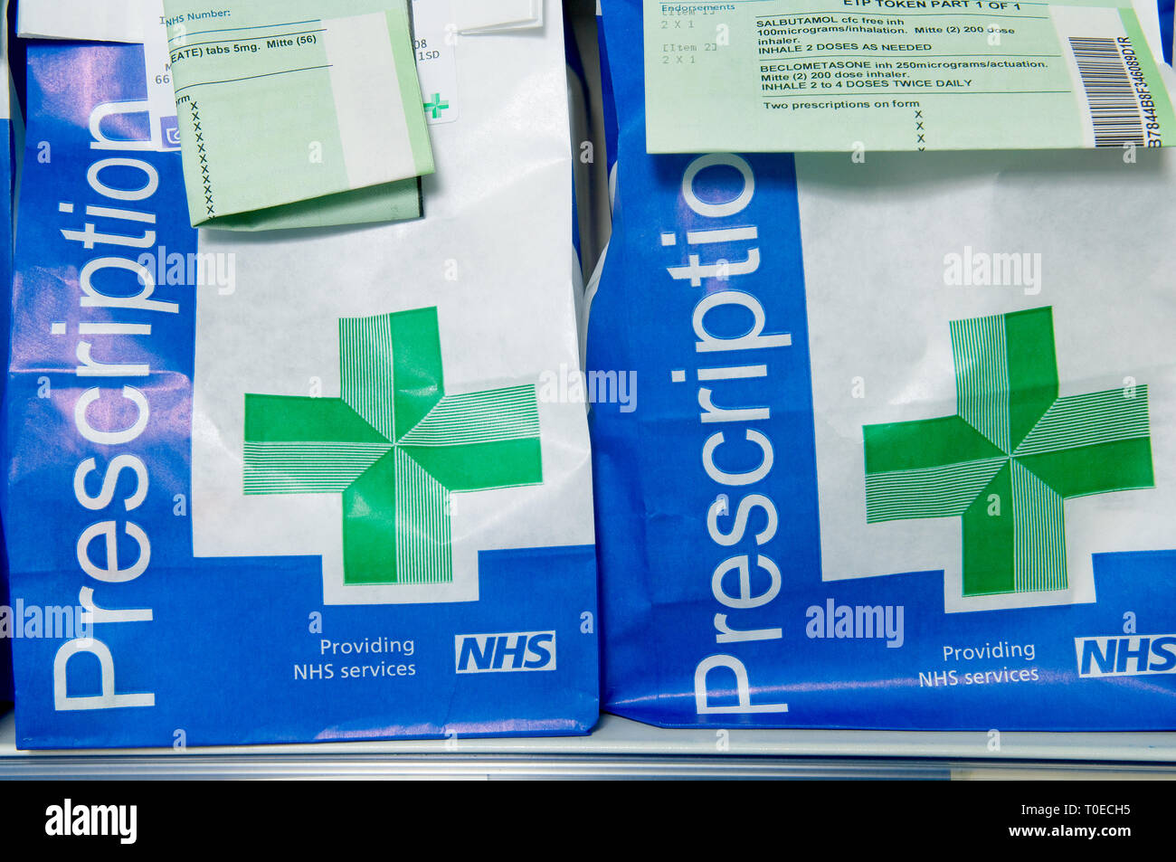 Paper bags of NHS prescriptions ready to collect with the prescription attached to ID the contents. - Stock Image