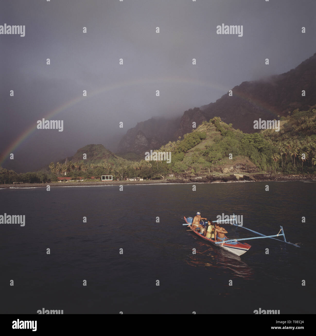 French Polynesia. Marquesas Islands. View of coast with outrigger canoe. - Stock Image