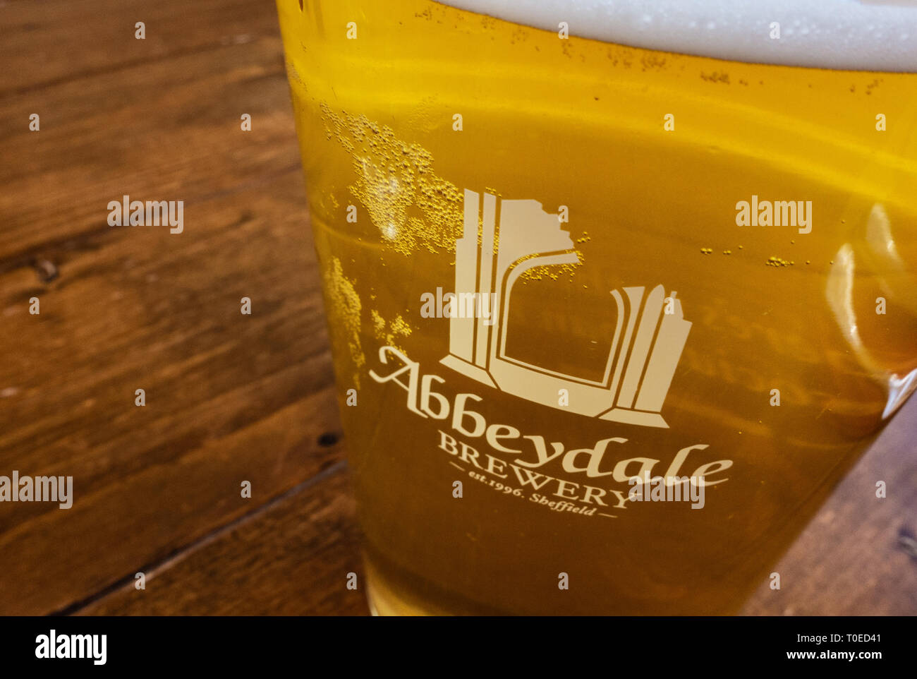 View looking downwards at a freshly drawn pint of Abbeydale brewed ale, showing the brewery logo - Stock Image