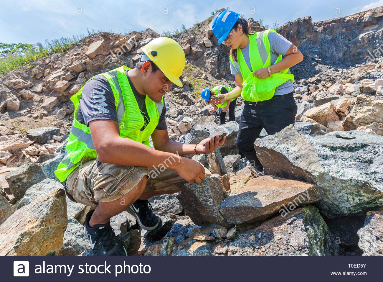 Geology and Earth science students study rocks and minerals in a quarry. - Stock Image