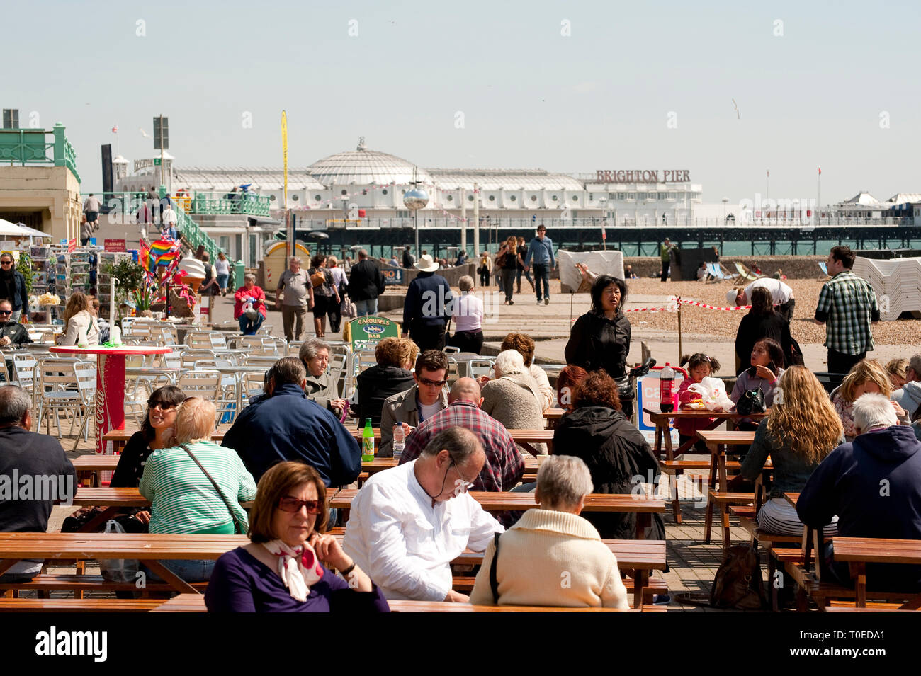 Holidaymakers enjoying refreshments sitting outside a cafe on the seafront in Brighton, Sussex, England. Stock Photo