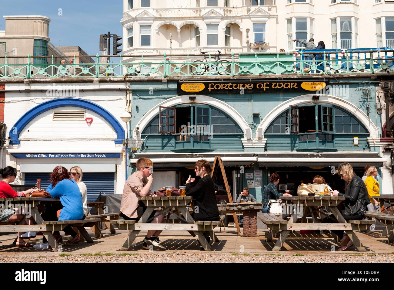 People sitting outside the Fortune of War bar on the seafront in Brighton, Sussex, England. - Stock Image