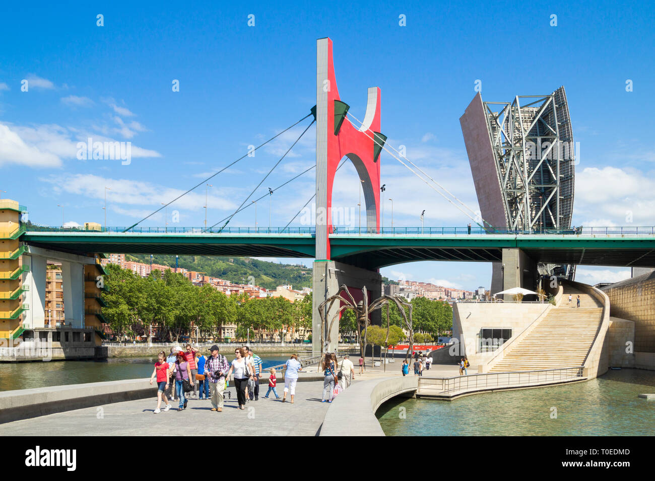 Tourists near spider sculpture 'Maman' by Louise Bourgeois under La Salve bridge outside Guggenheim museum in Bilbao, Spain. - Stock Image