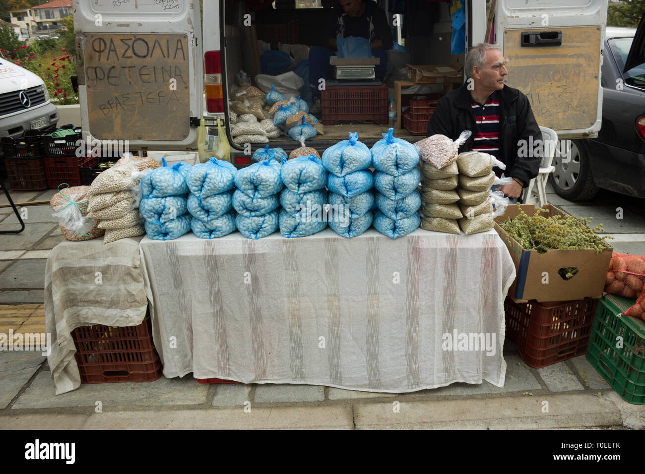 Greek stallholder sitting on a chair awaiting to sell his butter beans harvest to customers at the annual chestnuts festival. Leivadi, Greece - Stock Image