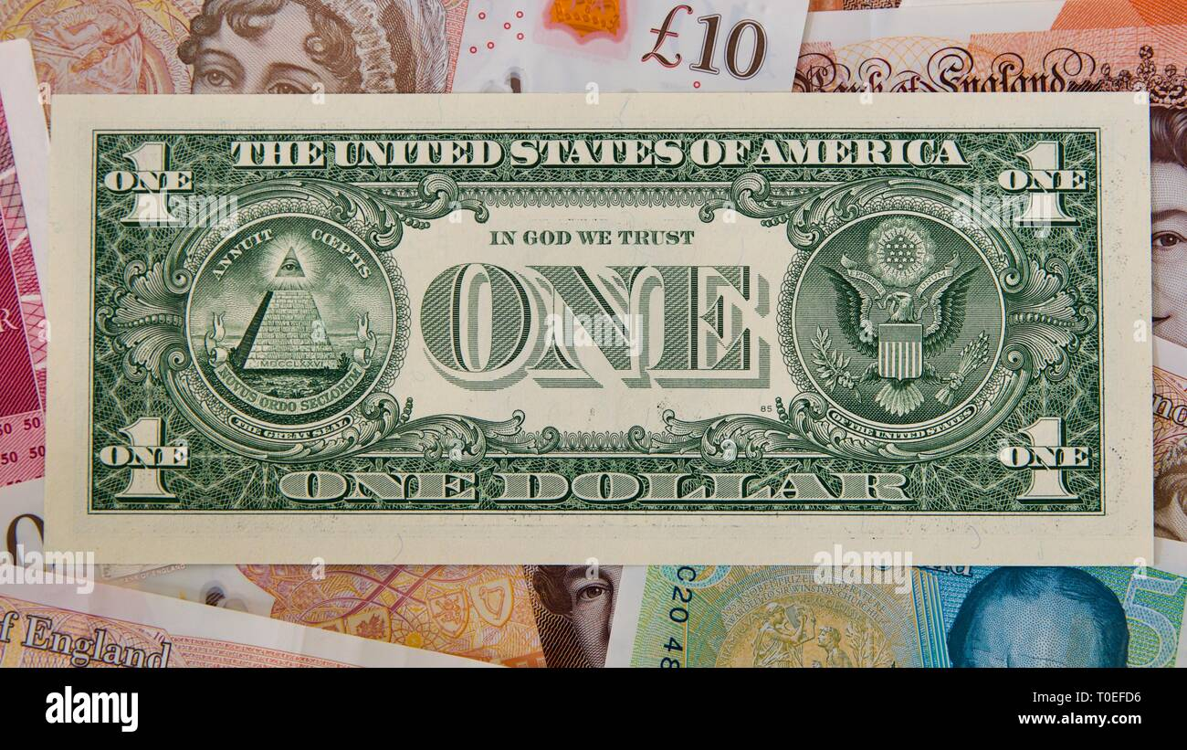 United States one-dollar bill with British banknotes in the background - Stock Image
