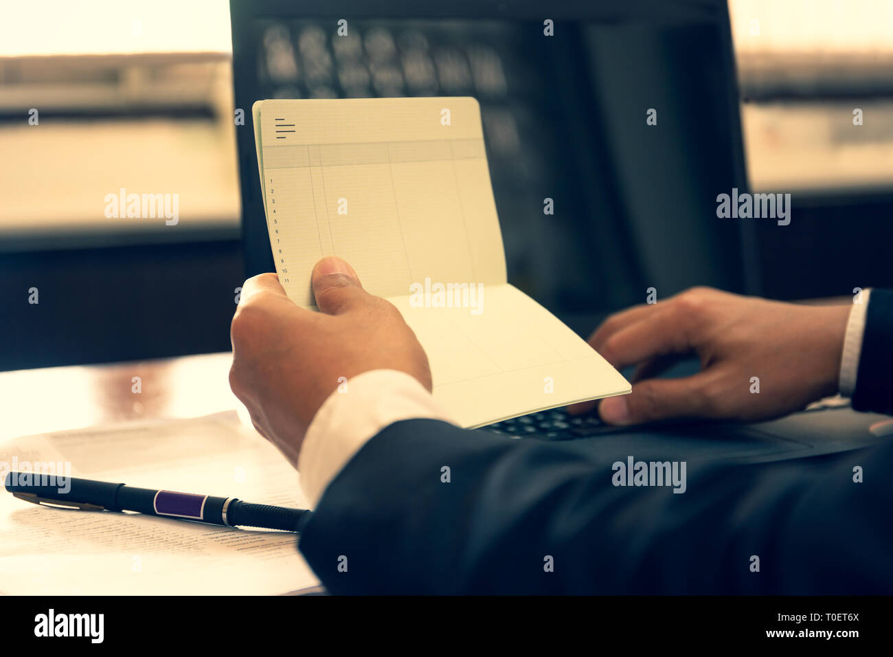 Business financial hand hold book statement and work with laptop. - Stock Image