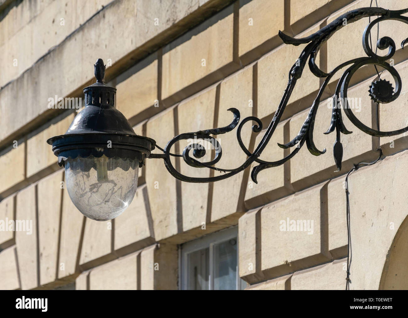 Ornate wrought iron lamp on lamp bracket on the facade of a house in Bath, England - Stock Image