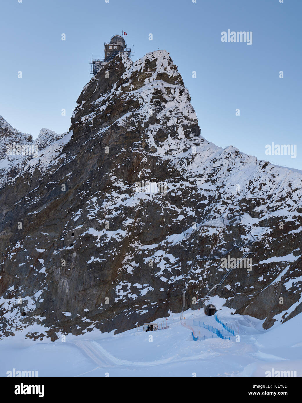 Unplugged in the Jungfrau region. A dusk view of the high altitude Sphinx Observatory viewed from a west side snow trail - Stock Image